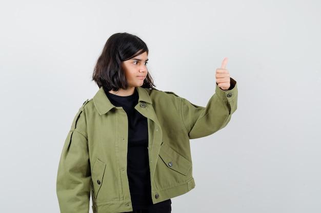 Tシャツ、緑のジャケットで親指を表示し、満足そうに見える10代の少女。正面図。