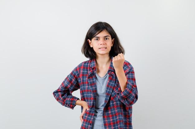 Ragazza teenager che mostra il gesto del vincitore in abiti casual e sembra fortunata, vista frontale.