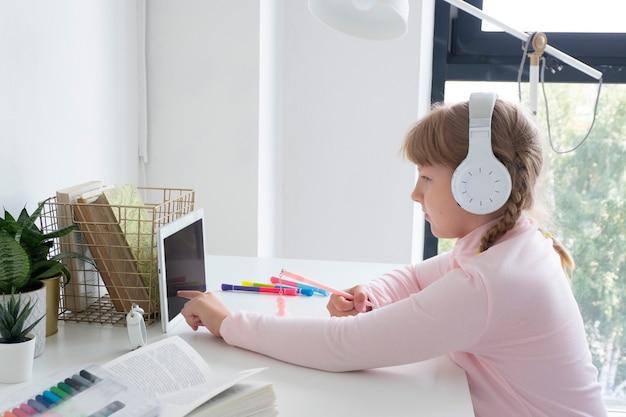 Девушка сидит за столом с планшетом и в наушниках и пишет в блокноте. концепция дистанционного обучения.