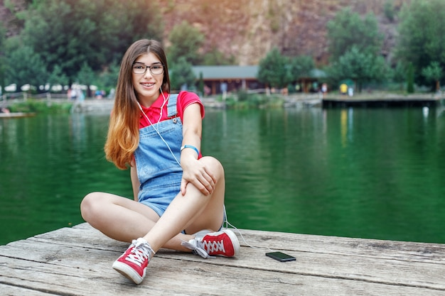 Teen girl sits at the lake in glasses.