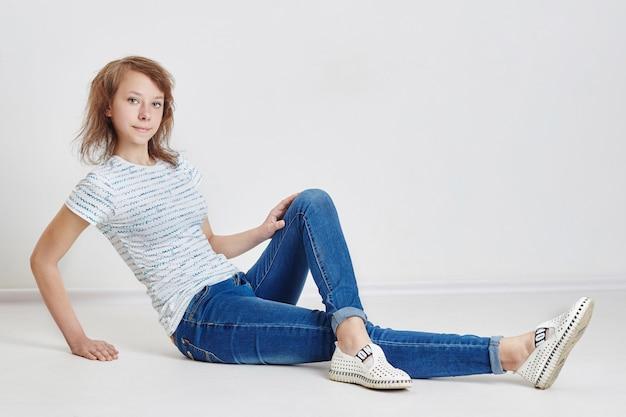 Teen girl sitting on floor posing. girl dreams