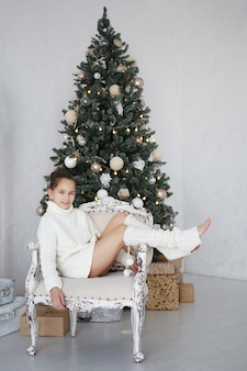 クリスマスツリーの近くの椅子に座っている十代の少女。白いニットのウールのセーターとレギンスを着ています。髪が束ねられています。嬉しい驚き。新年の贈り物。