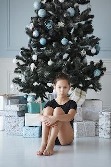 床の上のクリスマスツリーの近くに座っている十代の少女。体操用の黒いレオタードを着ています。髪が束ねられています。嬉しい驚き。新年の贈り物。
