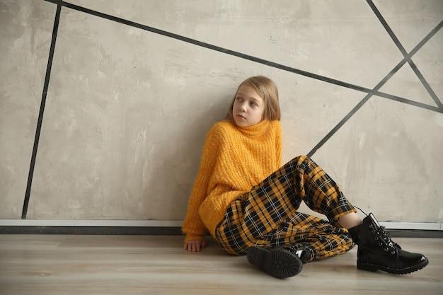 벽 근처에 앉아 십 대 소녀입니다.