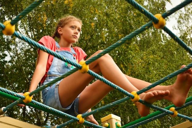 Девушка сидит на веревочной лестнице. проблемы в школе.