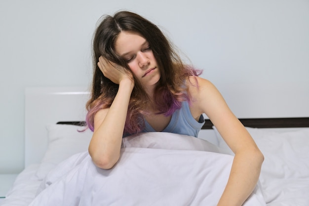 Teen girl sleeping at home in bed, morning asleep sitting