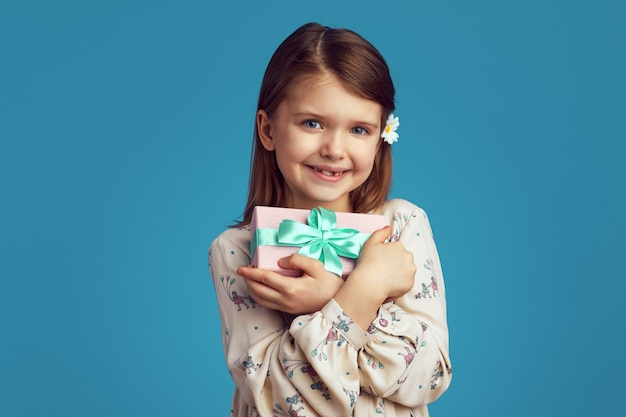 Девушка-подросток улыбается и обнимает упакованную подарочную коробку на синем фоне