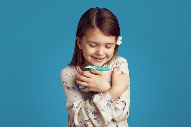 Девушка-подросток улыбается и обнимает упакованную подарочную коробку на синей стене