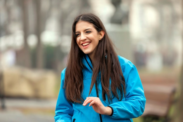 Teen girl smiling in green park in sunny summer evening