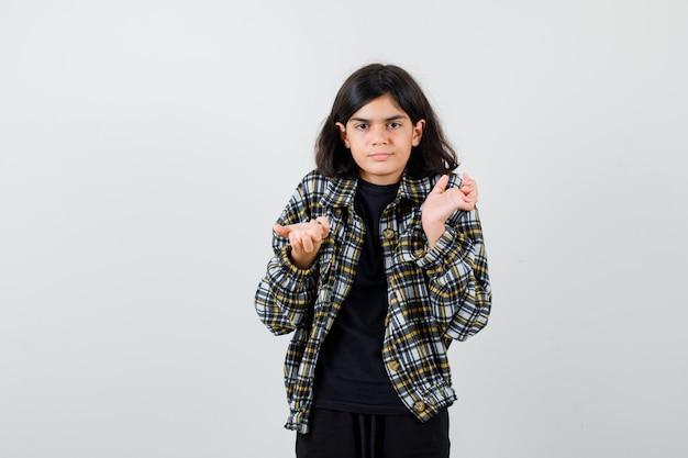10대 소녀는 캐주얼 셔츠에 무의식적인 몸짓으로 손바닥을 펼치고 수심에 찬 앞모습을 보고 있습니다.