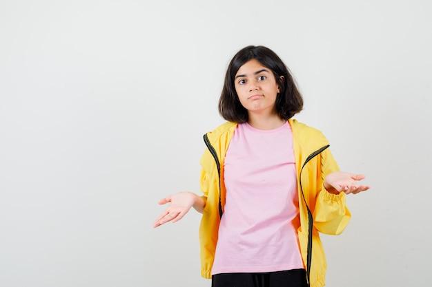 黄色のトラックスーツ、tシャツで手のひらを広げて困惑しているように見える10代の少女、正面図。