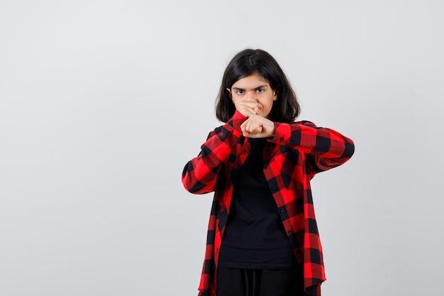 Девушка-подросток стоя в позе боя в повседневной рубашке и выглядела сосредоточенной. передний план.
