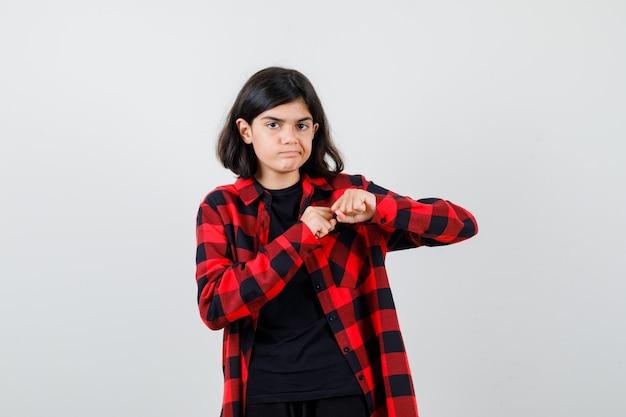 Девушка-подросток стояла в позе боя в футболке, клетчатой рубашке и выглядела безрассудно. передний план.