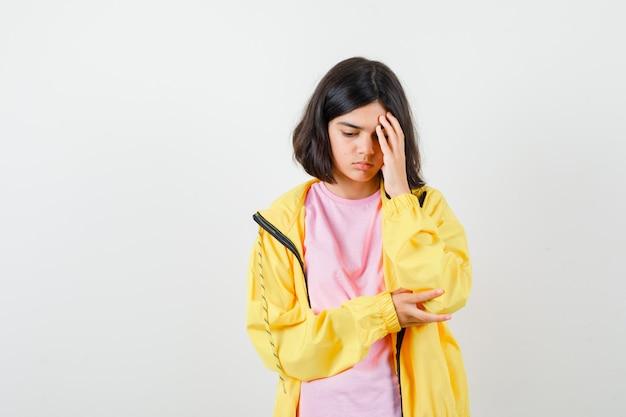 Tシャツ、黄色のジャケットでポーズを考えて立っていると困惑している10代の少女。正面図。