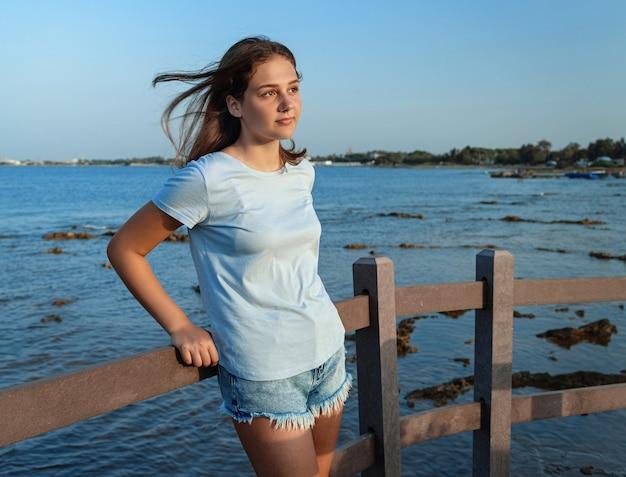 Девушка стоя на деревянном мосту у моря
