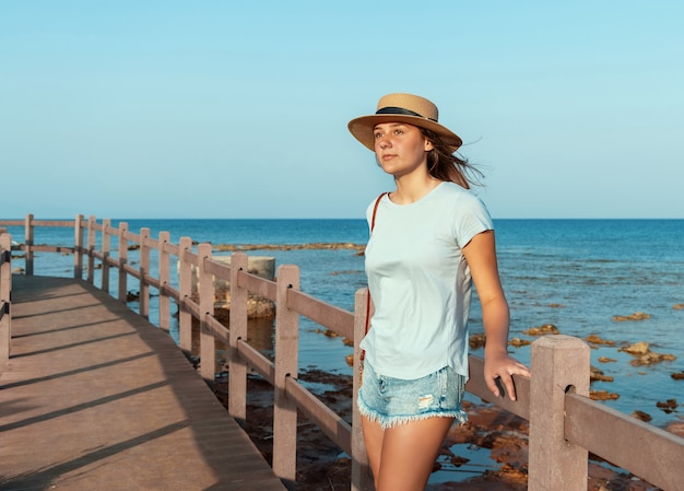 Девушка-подросток стояла на деревянной дорожке у моря на закате, в голубой футболке, соломенной шляпе и кошельке. концепция летнего путешествия