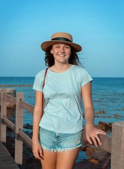 10대 소녀는 해가 질 때 바다 옆 나무 산책로에 서서 밝은 파란색 티셔츠, 밀짚모자, 지갑을 쓰고 있습니다. 여름 여행 개념