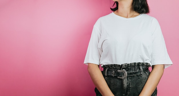 孤立した笑顔のカラフルな背景の上に立っている十代の少女。白いtシャツ、空白スペースtシャツコピースペース、デザイン、ショッピングコマーシャルショットに身を包んだ若い女性