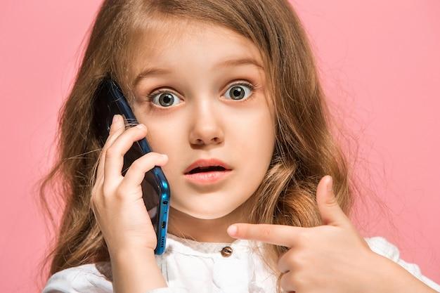 トレンディなピンクのスタジオの背景に携帯電話で笑って立っている十代の少女。