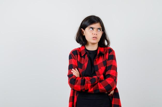 Девушка-подросток стояла со скрещенными руками в футболке, клетчатой рубашке и выглядела скучно, вид спереди.