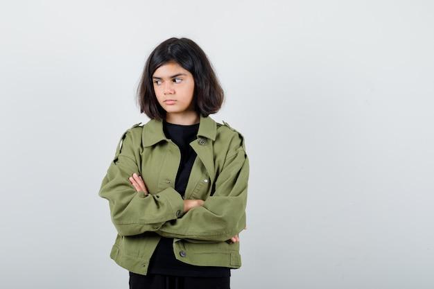 Tシャツ、緑のジャケット、物思いにふける腕を組んで立っている10代の少女。正面図。