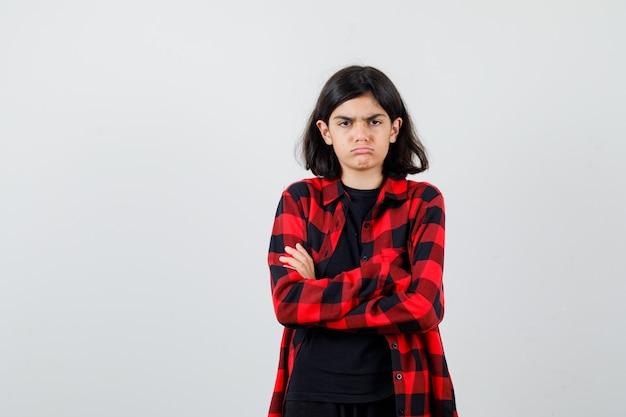 Ragazza teenager in piedi con le braccia incrociate in t-shirt, camicia a scacchi e guardando risentita, vista frontale.