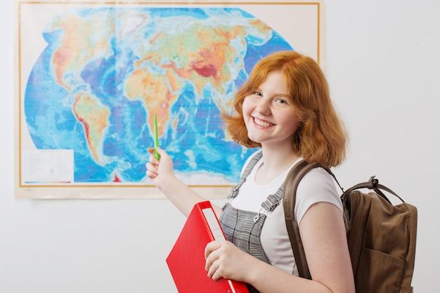 Девочка-подросток стоит на географической карте