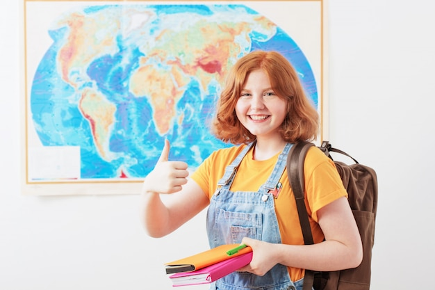 地理的な地図に立っている十代の少女