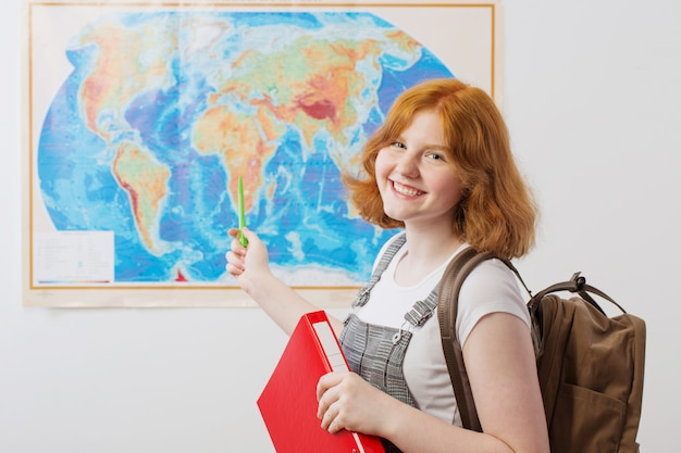 Teen girl stands at geographical map