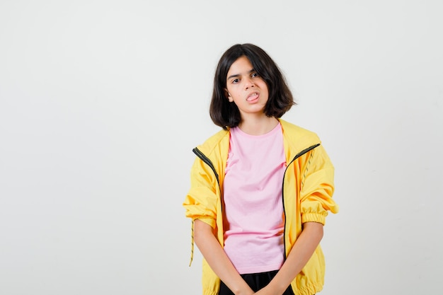 Teen girl sticking tongue out in t-shirt, jacket and looking bored , front view.