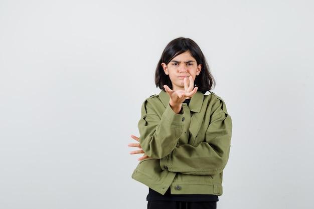 Девушка-подросток протягивает руку в вопросительном жесте в футболке, куртке и выглядит серьезным, вид спереди.
