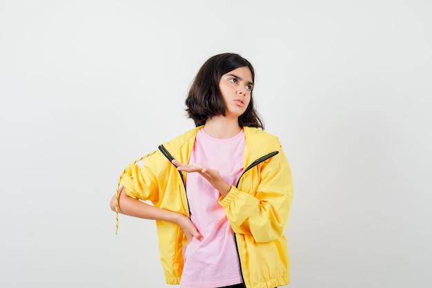 Девушка-подросток вопросительно протягивает руку, смотрит в футболку, куртку и задумчиво. передний план.