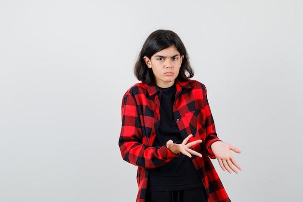 Девушка-подросток протягивает руки в вопросительном жесте в футболке, клетчатой рубашке и выглядит серьезно. передний план.