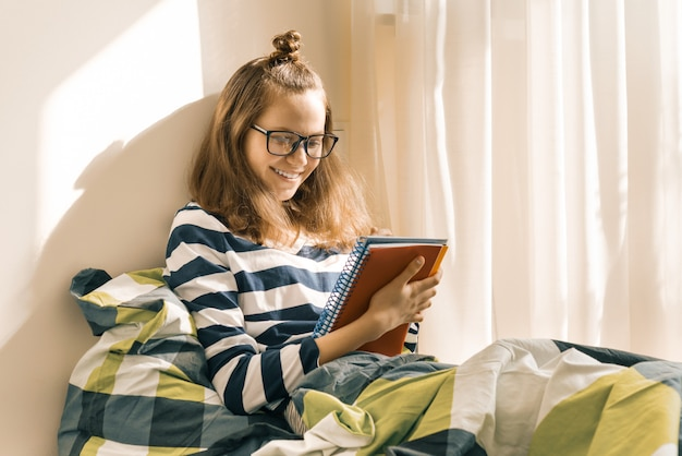 Teen girl studying at home sitting in bed