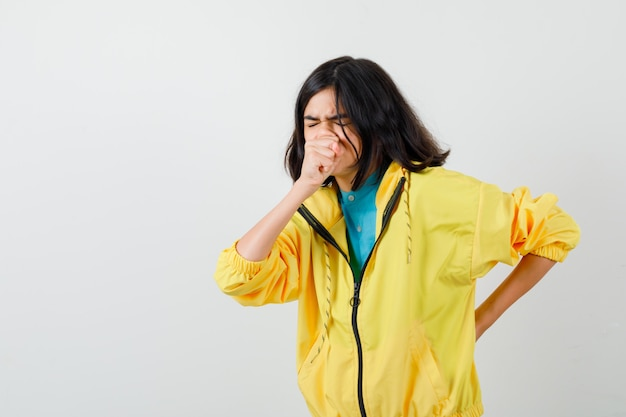 黄色のジャケットで咳に苦しんでいる10代の少女と病気に見えます。正面図。