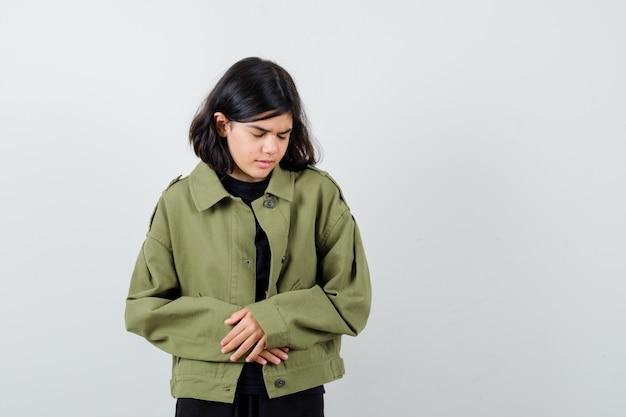 Tシャツ、緑のジャケットで腹痛に苦しんでいて、痛みを伴うように見える10代の少女。正面図。