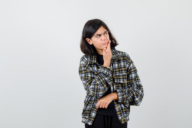 歯痛に苦しんでいる10代の少女、カジュアルなシャツを着て脇を見て、痛みを伴うように見えます。正面図。