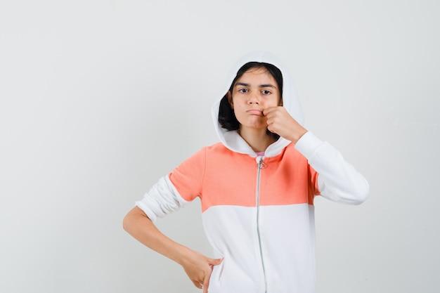 Teen girl in sweatshirt showing zip gesture.