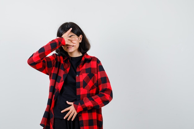 Teen girl in t-shirt, checkered shirt holding hand on face and looking sorrowful , front view.