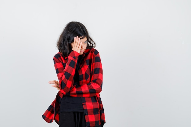 Teen girl in t-shirt, checkered shirt holding hand near face and looking anxious , front view.