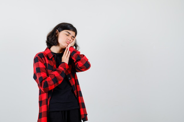 Teen girl in t-shirt, checkered shirt leaning on hand as pillow and looking sleepy , front view.