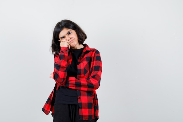 Teen girl in t-shirt, checkered shirt propping cheek on hand and looking disappointed , front view.