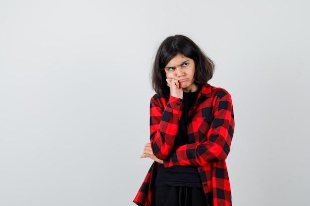 Ragazza teenager in t-shirt, camicia a scacchi che puntella la guancia a portata di mano e sembra dispettosa, vista frontale.