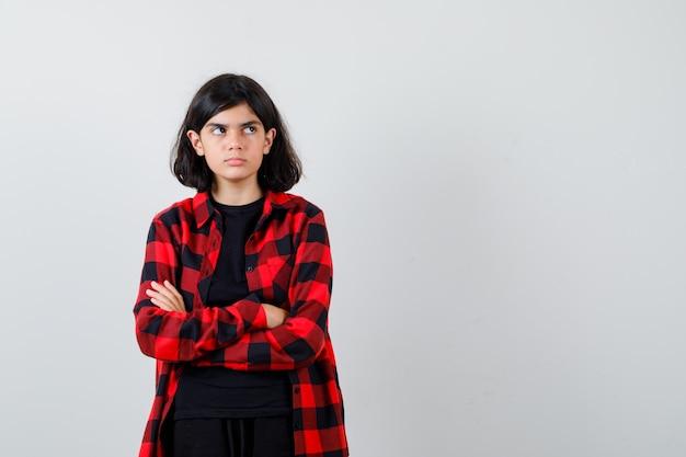 Ragazza teenager in t-shirt, camicia a scacchi in piedi con le braccia incrociate e guardando risentita, vista frontale.