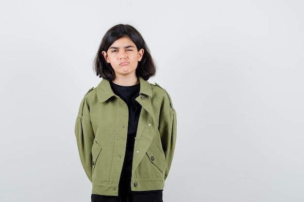 Teen girl in t-shirt, green jacket closing one eye while curving lips, holding hands behind back and looking dissatisfied , front view.