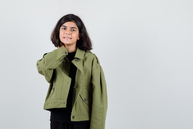 Ragazza teenager in maglietta, giacca verde che tiene la mano sul collo e sembra gioiosa, vista frontale.