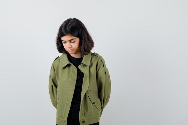 Ragazza teenager in t-shirt, giacca verde che si tiene per mano dietro la schiena mentre guarda in basso e sembra pensierosa, vista frontale.