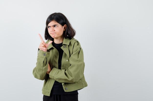 Ragazza teenager in maglietta, giacca verde che punta via e sembra seria, vista frontale.