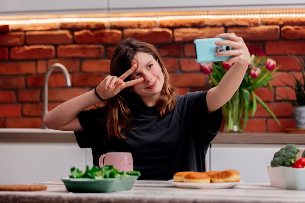 Teen girl takes a selfie in the kitchen