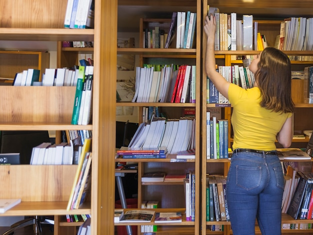 Teen girl taking book from top of bookcase